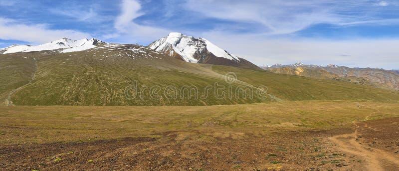 与康Yatze山的美好的全景风景和从Gongmaru La下面的一辆驴有蓬卡车通过,喜马拉雅山,拉达克,印度 免版税库存图片