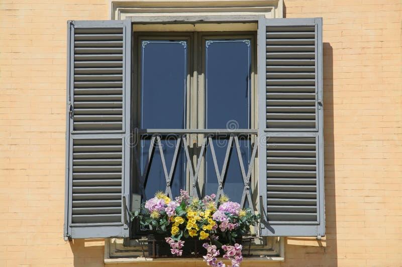 与开放快门的窗口,装饰用花,罗马,意大利 免版税库存图片