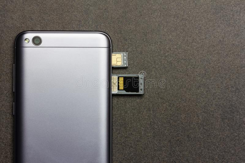 与开放槽孔的中国智能手机小米Redmi 5A银纳诺希姆卡片的,微SD驾驶顶视图的后部关闭在灰色b 免版税库存图片