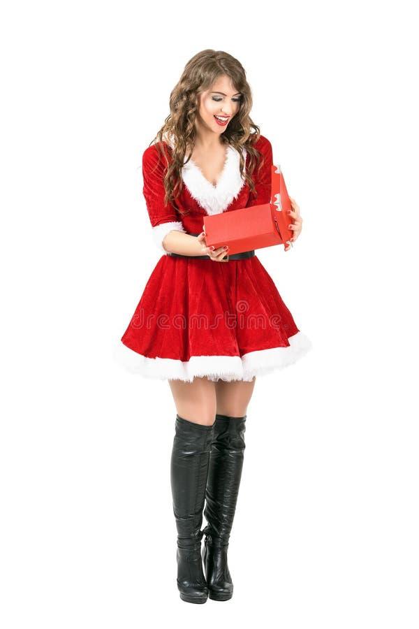 与开放的嘴的愉快的激动的圣诞老人妇女开头圣诞节礼物 免版税库存图片