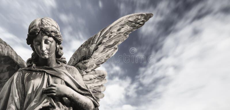 与开放翼的哀伤的守护天使雕塑隔绝与被弄脏的白色云彩剧烈的天空 哀痛天使哀伤的表示sculptur 免版税库存图片
