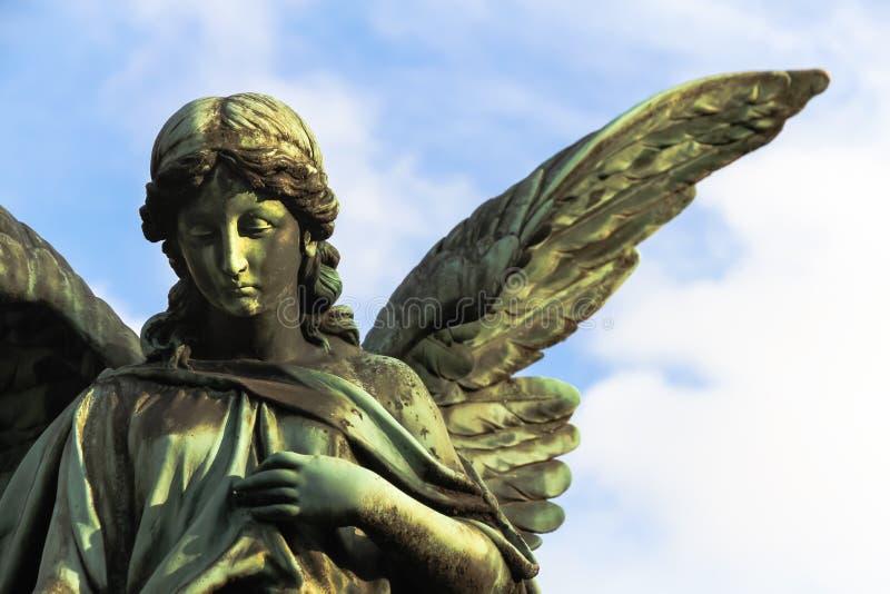 与开放长的翼的哀伤的守护天使铜雕塑横跨反对明亮的蓝色白色天空的框架 库存图片