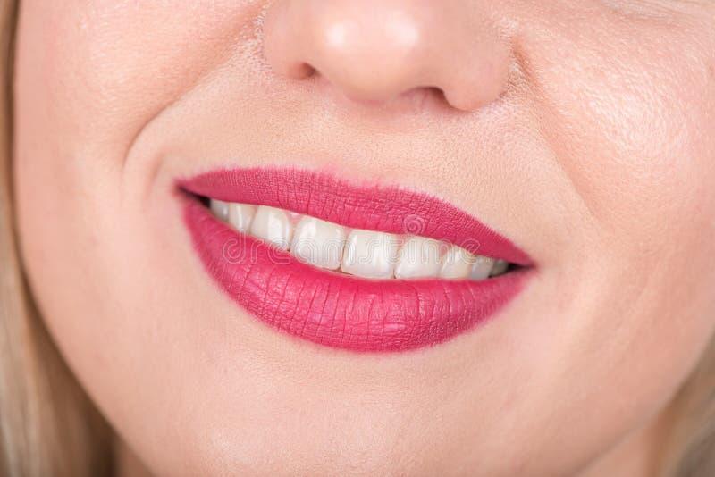 与开放嘴的愉快的妇女面孔 明亮的红色唇膏在使用中 空白的牙 工作室照片 免版税库存照片