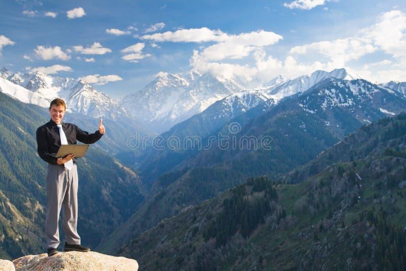 与开朗的笑的年轻商人在山上面 免版税库存图片