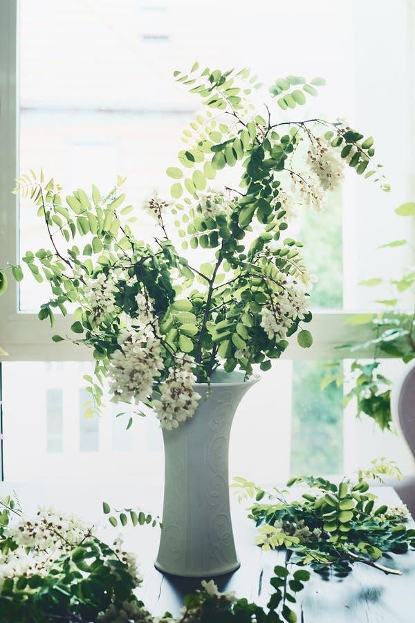 与开花的开花的花束在桌上的花瓶分支在窗口 舒适家庭内部和设计 免版税库存照片
