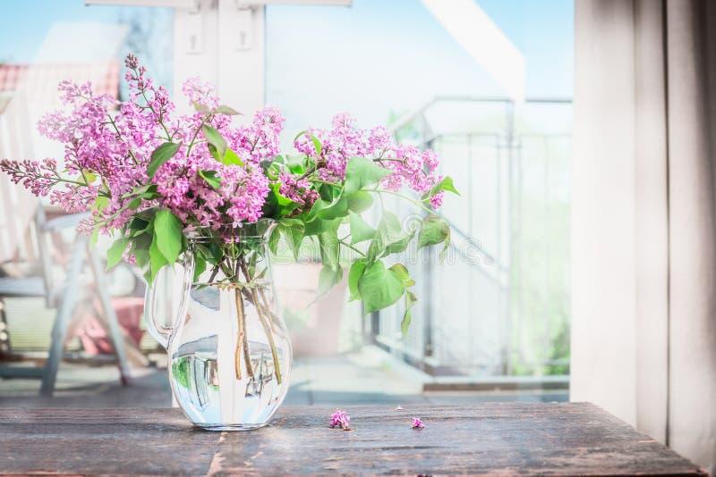 与开花的淡紫色花花束的家内部在桌上的 库存照片