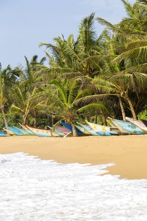 与异乎寻常的可可椰子树的热带海滩和在沙子的木小船在海水附近挥动 库存照片