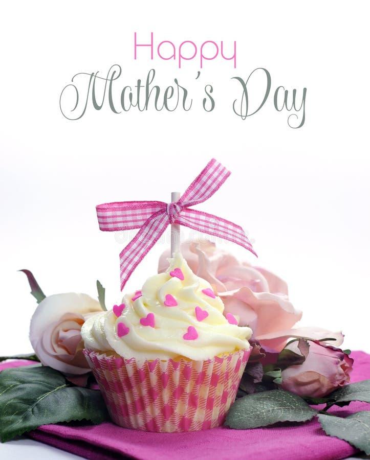 与弓、心脏和花的美丽的桃红色和白色杯形蛋糕与愉快的母亲节 免版税库存照片
