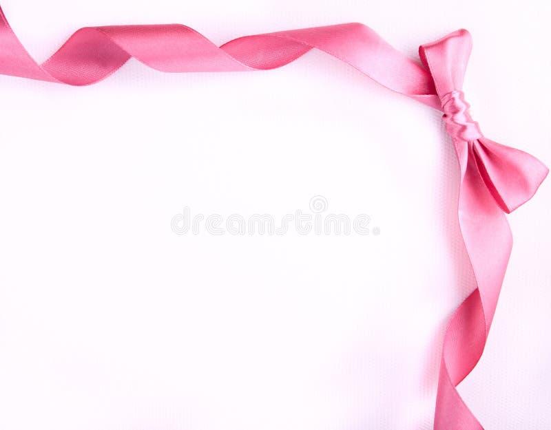 与弓的桃红色丝带在白色背景 免版税库存照片