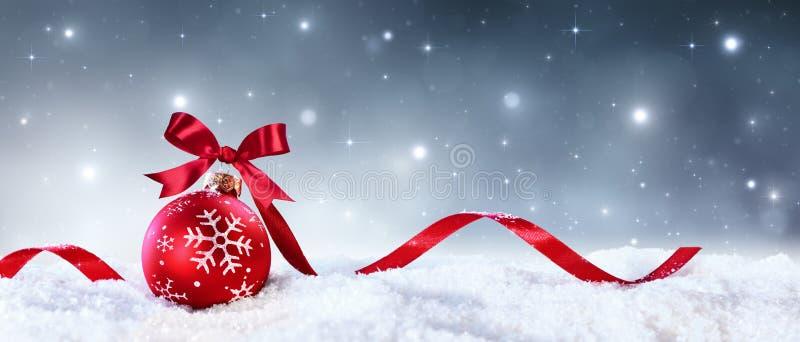 与弓的红色在雪的球形和丝带 免版税库存图片