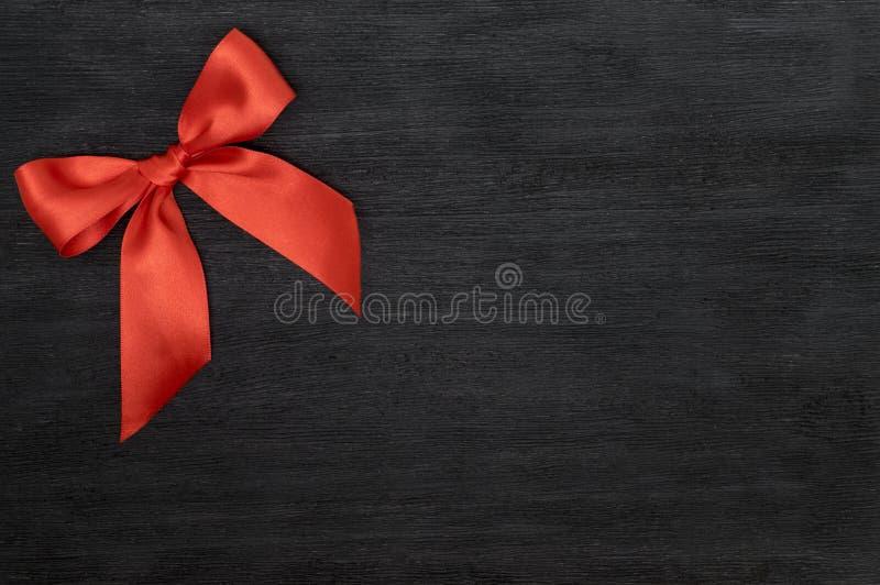 与弓的红色缎丝带在黑背景 免版税图库摄影
