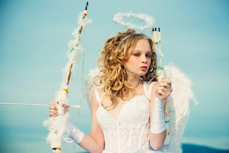 与弓箭的丘比特逗人喜爱的天使 一点反对晴朗的天空的天使女孩 从不可思议的故事的真正的神仙 天使女孩 免版税图库摄影