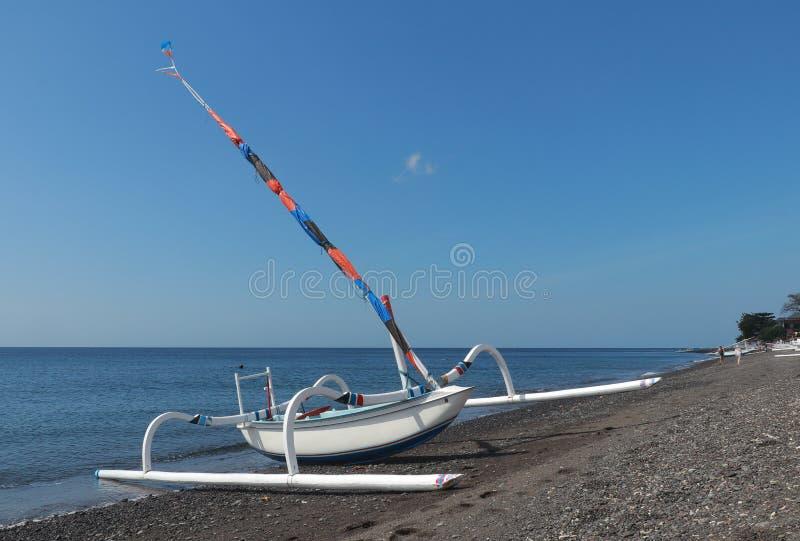 与引擎和风帆的传统渔船jukung 在与黑火山的沙子的海滩停放的巴厘语小船 波浪洗涤t 免版税库存照片