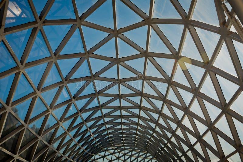 与弯曲屋顶和玻璃钢专栏的现代大厦 在透视的栅栏的几何抽象背景 钢结构g 图库摄影