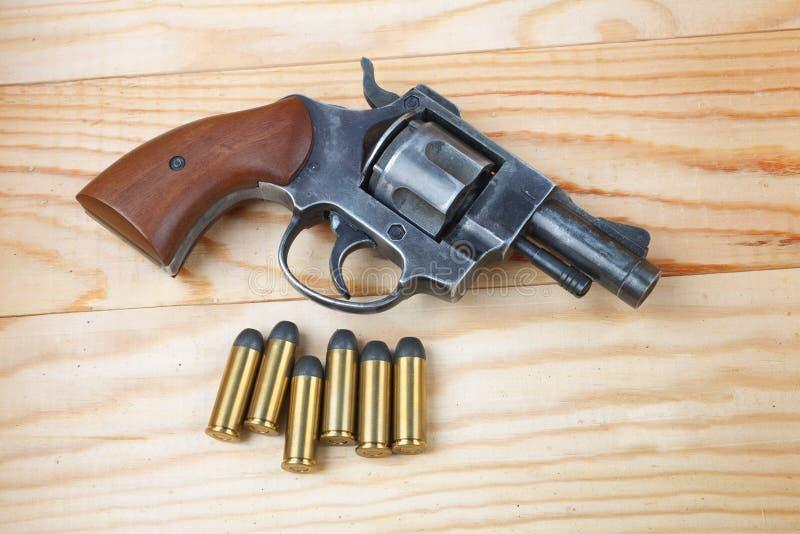 与弹药的左轮手枪在桌上 免版税库存照片