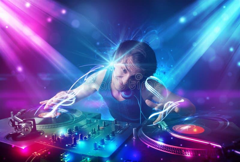 与强有力的光线影响的精力充沛的Dj混合的音乐 库存例证