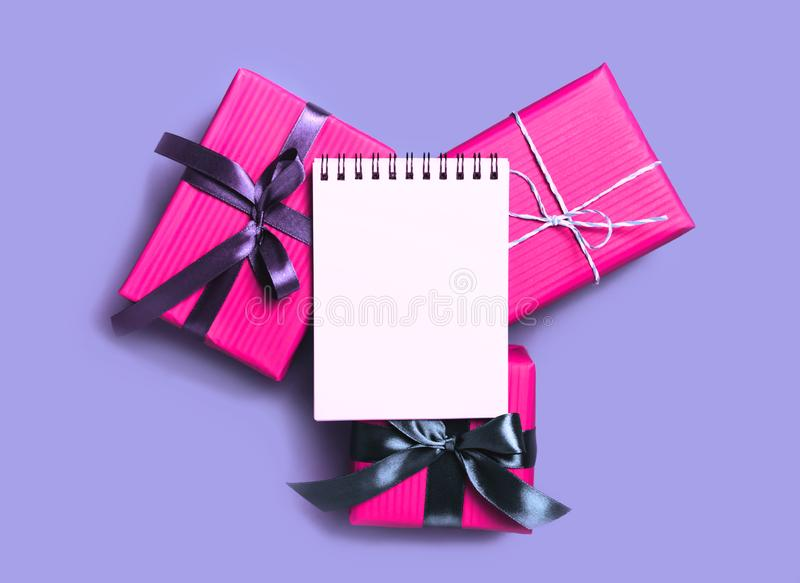 与当前礼物盒和空的笔记本的最小的圣诞节背景 库存图片