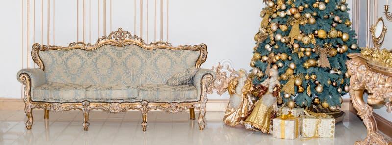 与当前箱子的美丽的装饰的金黄圣诞树在豪华经典内部 免版税库存图片