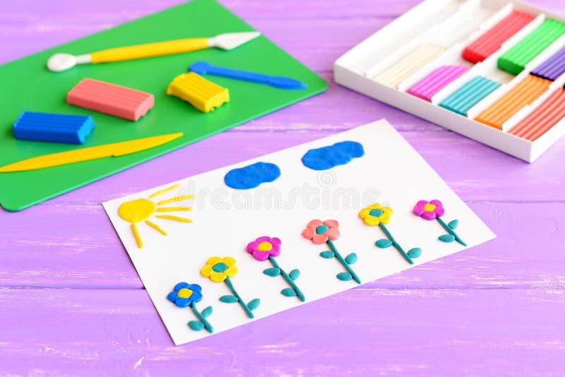 与彩色塑泥花、太阳和云彩的卡片 在一张木桌上设置的彩色塑泥 儿童雕塑黏土艺术 制作想法 免版税库存图片