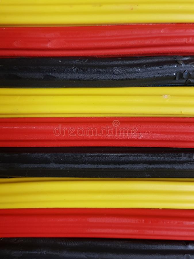 与彩色塑泥酒吧的摘要在黑,黄色和红颜色、背景和纹理 免版税库存图片