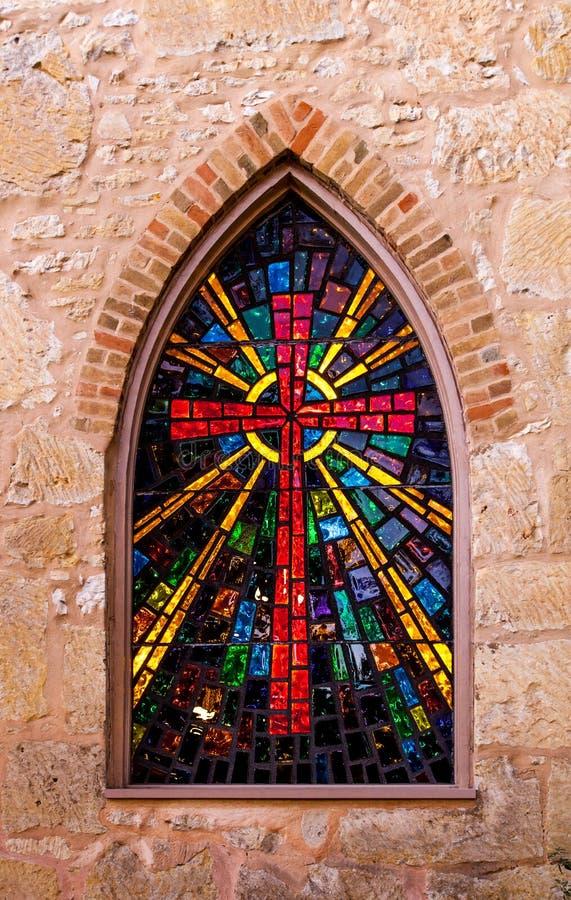 与彩色玻璃红十字的哥特式样式教会窗口被做  库存图片