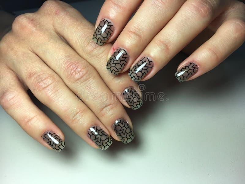 与彩色玻璃设计的时兴的黑修指甲 免版税库存图片