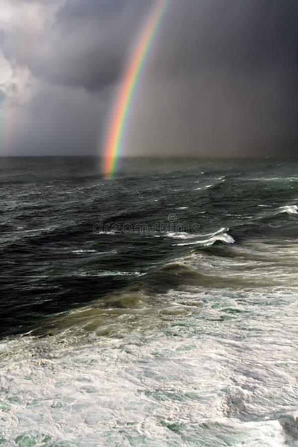 与彩虹和风大浪急的海面的风暴 免版税图库摄影