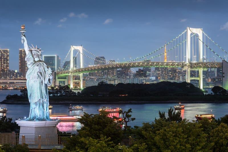 与彩虹桥梁的Odaiba自由女神像和东京在晚上耸立 免版税库存照片