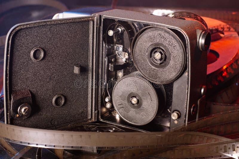与影片轴的老电影摄影机在桌上 免版税库存照片
