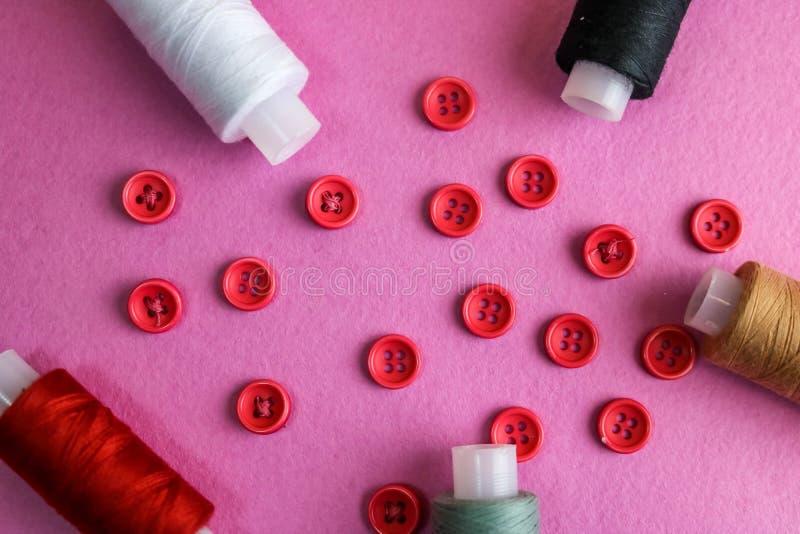 与很多圆的红色按钮的美好的框架缝合,螺纹短管轴针线和丝球的  复制空间 平的位置 库存照片