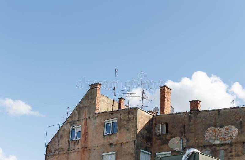 与很多模拟电视天线的老被破坏的修造的屋顶登上了对此反对与云彩的天空蔚蓝 免版税库存照片
