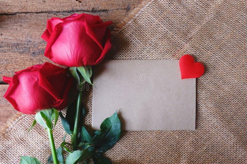 与微型心脏的红色玫瑰和在木地板上的纸牌 Valentine& x27的语篇框架图;s概念 免版税库存照片