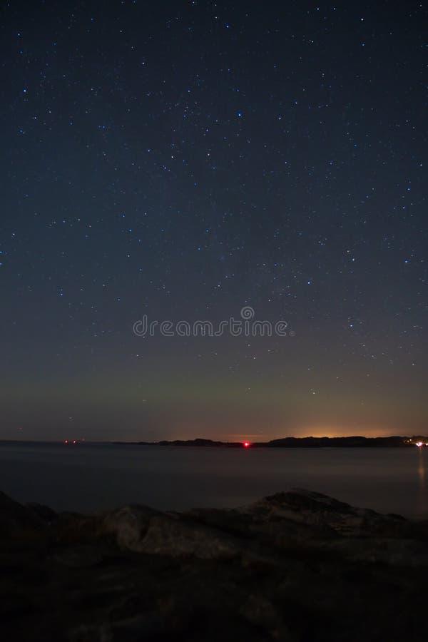 与微弱的北极光极光borealis的夜空-西挪威 免版税库存图片