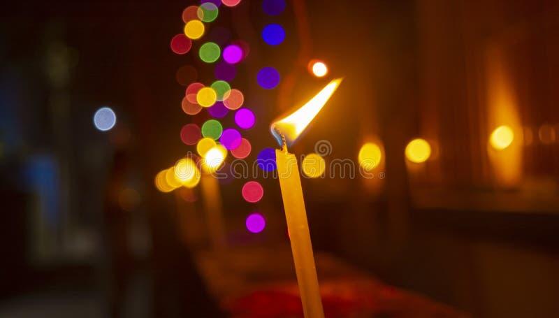 与微弱的色的光的燃烧的蜡烛在背景中 免版税图库摄影