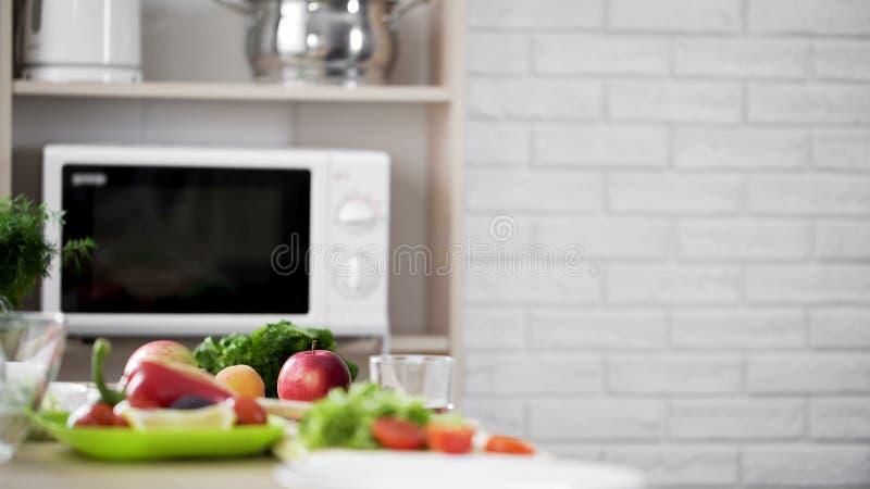 与微波炉的厨房视图和新鲜蔬菜和果子在桌上 免版税库存照片