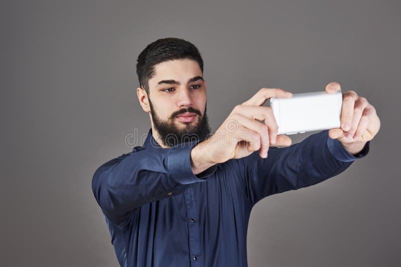 与微笑和看电话的巧妙的电话的年轻有胡子的行家商人谈的selfie照片反对灰色 库存图片