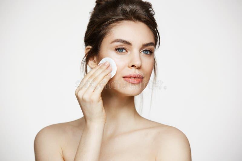 与微笑在白色背景的棉花海绵的美丽的自然深色的女孩清洁面孔 整容术和温泉 免版税库存照片
