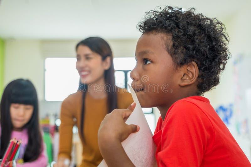 与微笑对背景的老师的非裔美国人的种族孩子在幼儿园教室 免版税库存图片