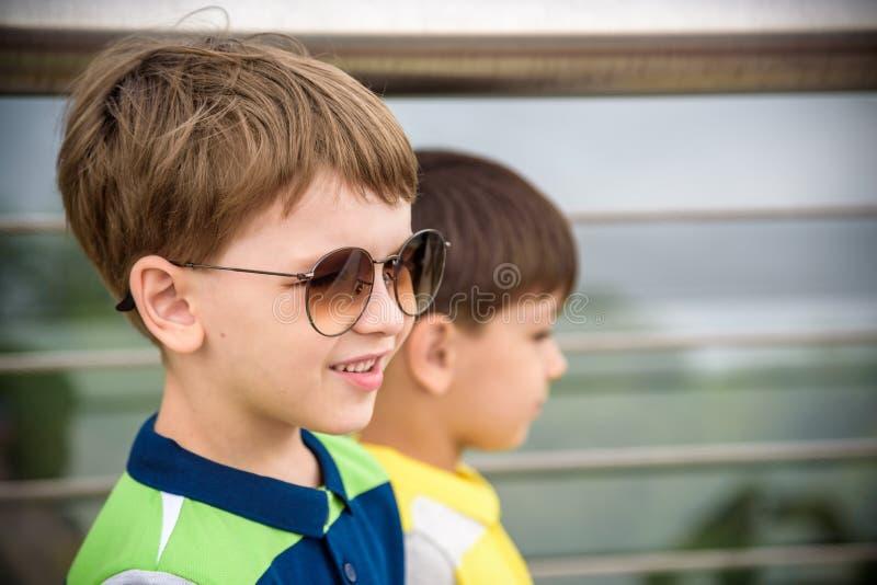 与微笑的孩子画象,在Sunglases享受夏天休假特写镜头,夏天户外,滑稽的孩子的愉快的男孩的接近的面孔 免版税库存图片