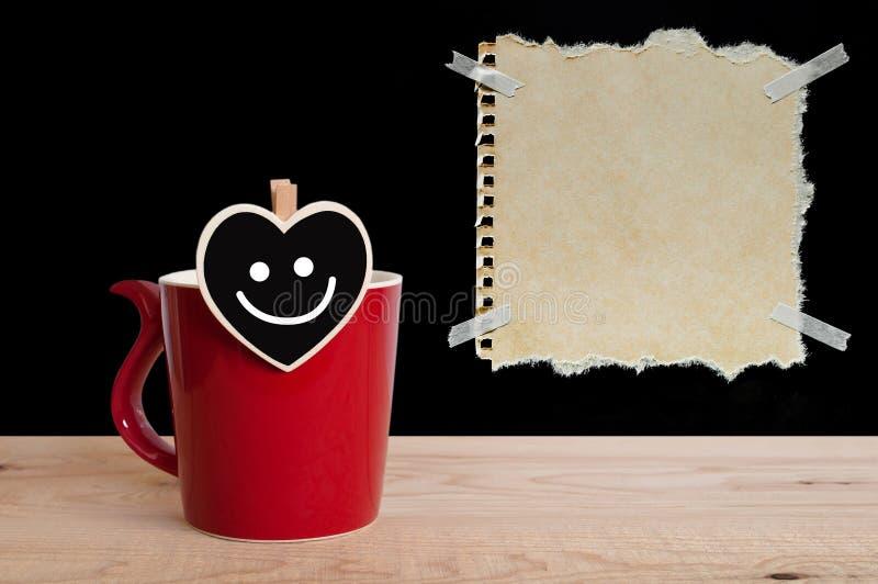 与微笑的红色杯子咖啡在心脏板和与纸带的包装纸在黑板和木背景 库存照片