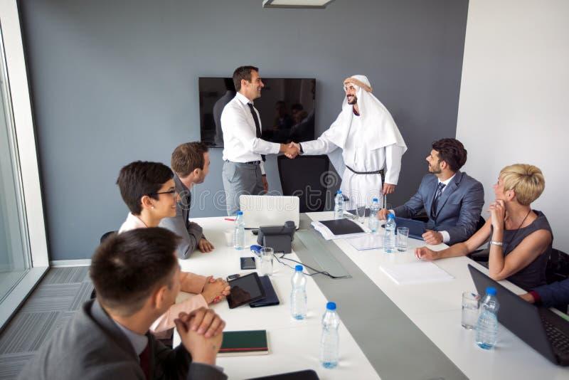 与微笑的阿拉伯pa的微笑的成功的商人握手 库存图片