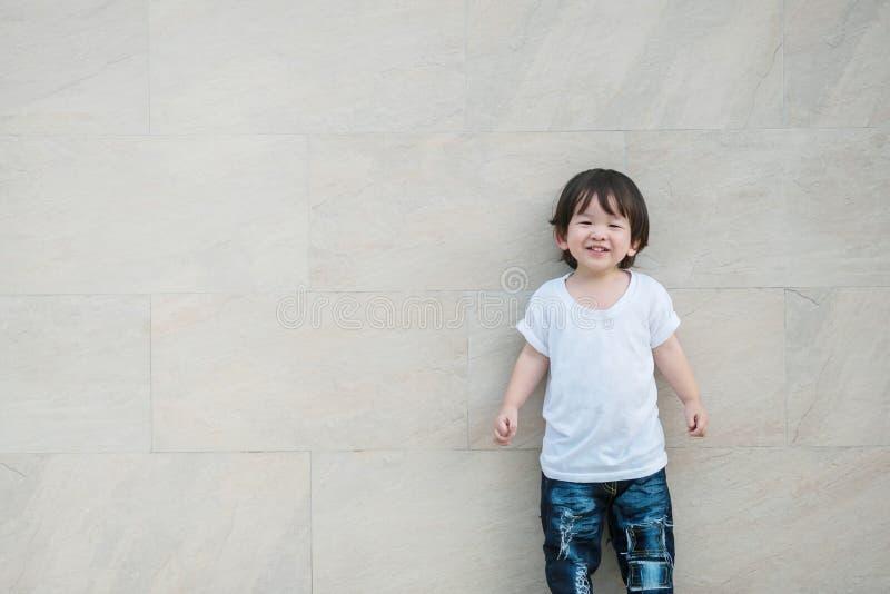 与微笑面孔的特写镜头愉快的亚洲孩子在大理石石墙上构造了与拷贝空间的背景 免版税库存照片