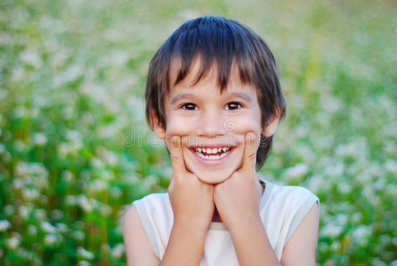 与微笑鬼脸的逗人喜爱的孩子 图库摄影