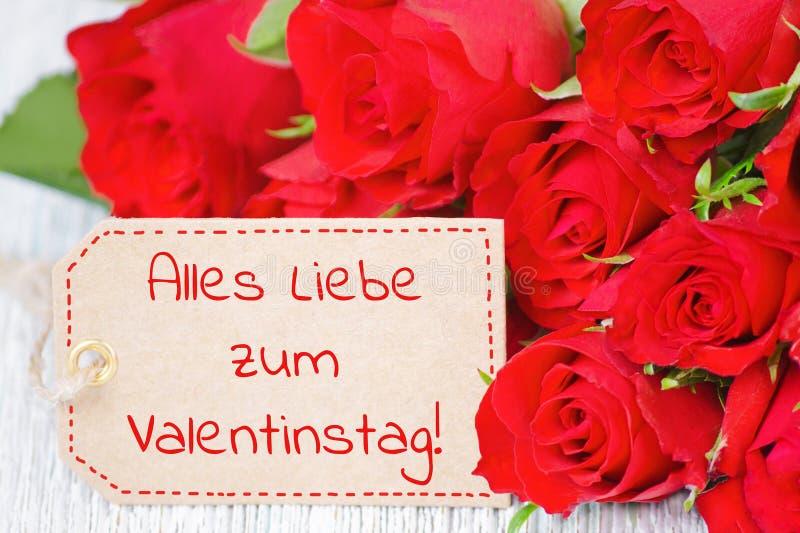 与德国文本愉快的情人节和红色玫瑰的标签开花 免版税库存照片