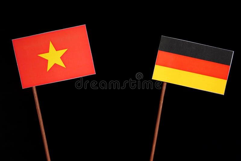与德国旗子的越南旗子在黑色 库存图片