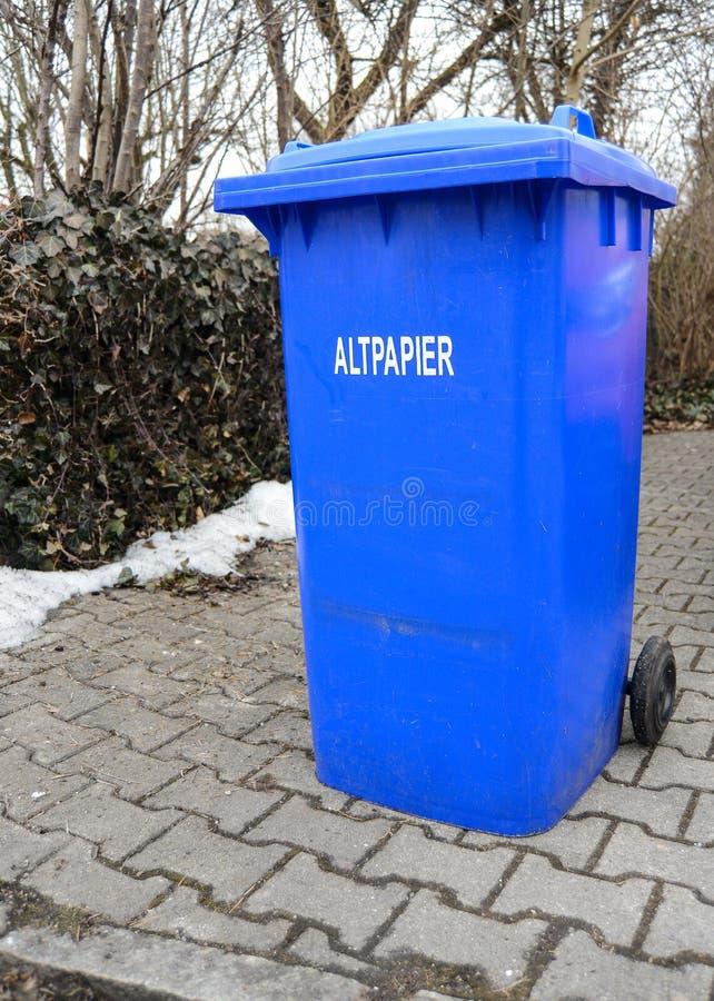 与德国标志读的Wastepaper的蓝色废物箱 库存图片