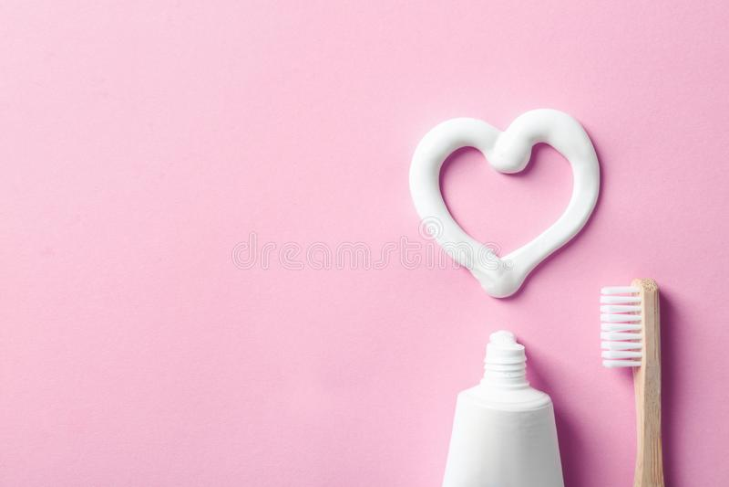 与心形的平的被放置的构成由牙膏和空间制成文本的在颜色背景 库存图片