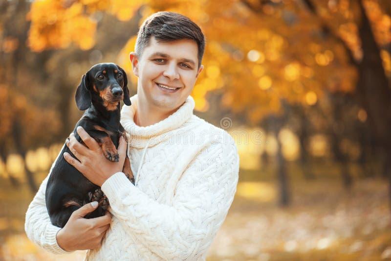 与心爱的狗的愉快的业余时间!停留在秋天公园的英俊的年轻人微笑和拿着逗人喜爱的小狗达克斯猎犬 库存图片