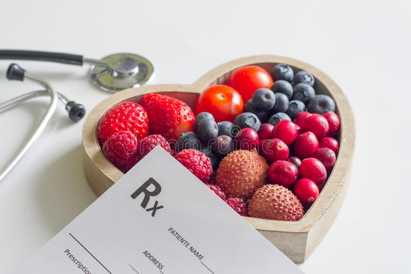 与心脏听诊器和医疗处方概念的健康饮食 免版税库存照片