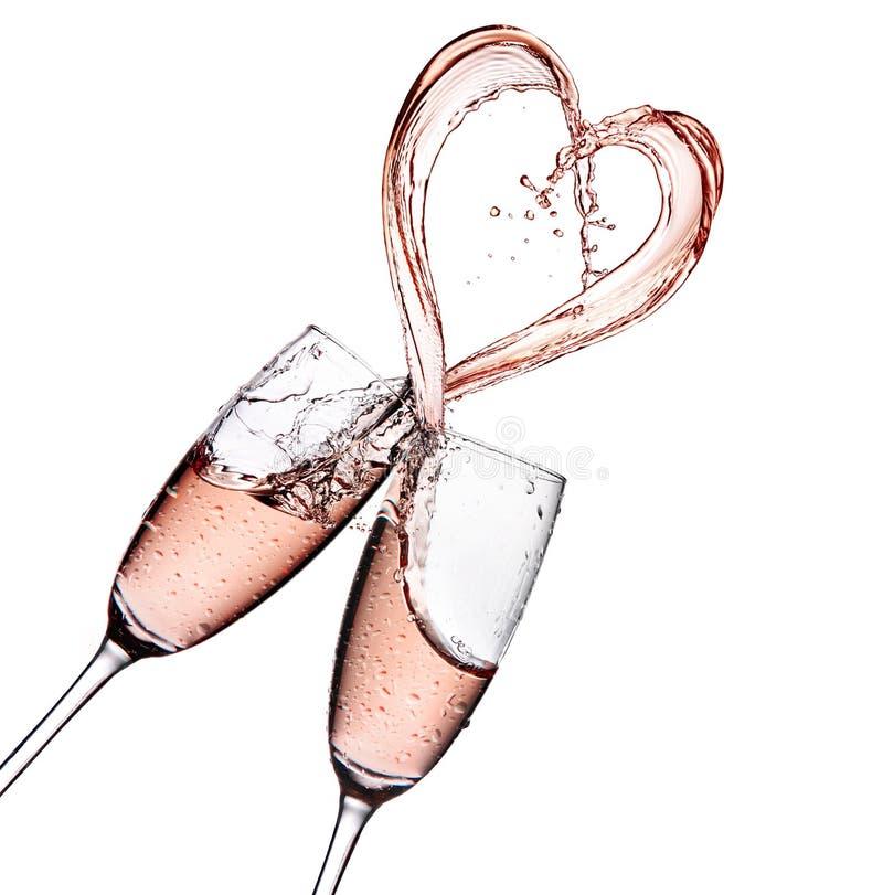 与心脏在白色背景隔绝的形状飞溅的罗斯香槟 免版税库存照片